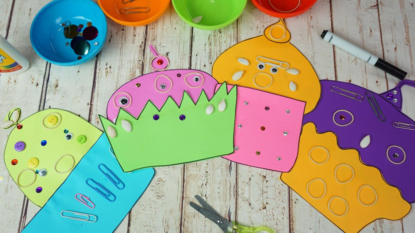 Colorful cupcake shapes made out of paper and decorated with colorful sequins, rubber bands, buttons, google eyes and paper clips.