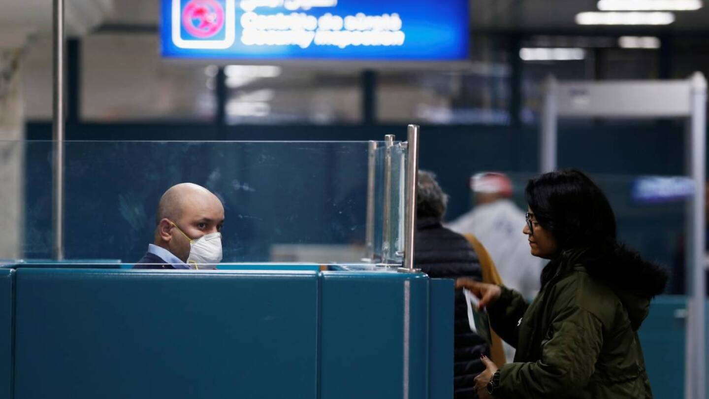ARCHIVE PICTURE: An officer of the Tunisian State Border Guard Service wearing a protective mask checks the passport of a passenger, as a precautionary measure to avoid contracting coronavirus work at Tunisia Airport in Tunis, Tunisia February 29, 2020. REUTERS/Zoubeir Souissi