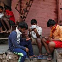 A group of boys look at their mobile phones, during a nationwide lockdown in India to slow the spread COVID-19, in Dharavi, one of Asia's largest slums, during the coronavirus disease outbreak, in Mumbai, India, April 9, 2020.