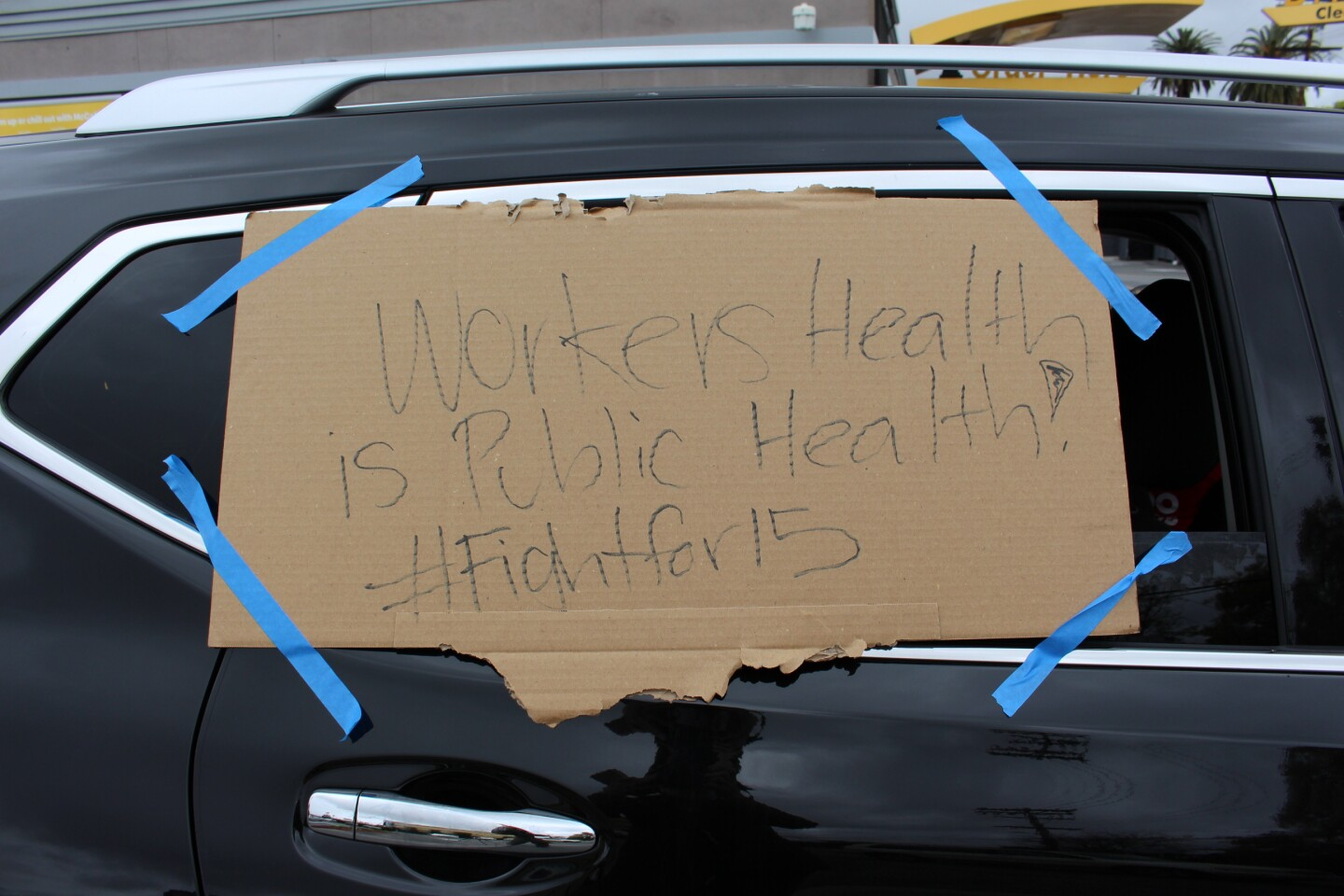 "Sign reading ""Workers Health is Public Health #Fightfor15"" on car window during protest at McDonalds on April 6, 2020 