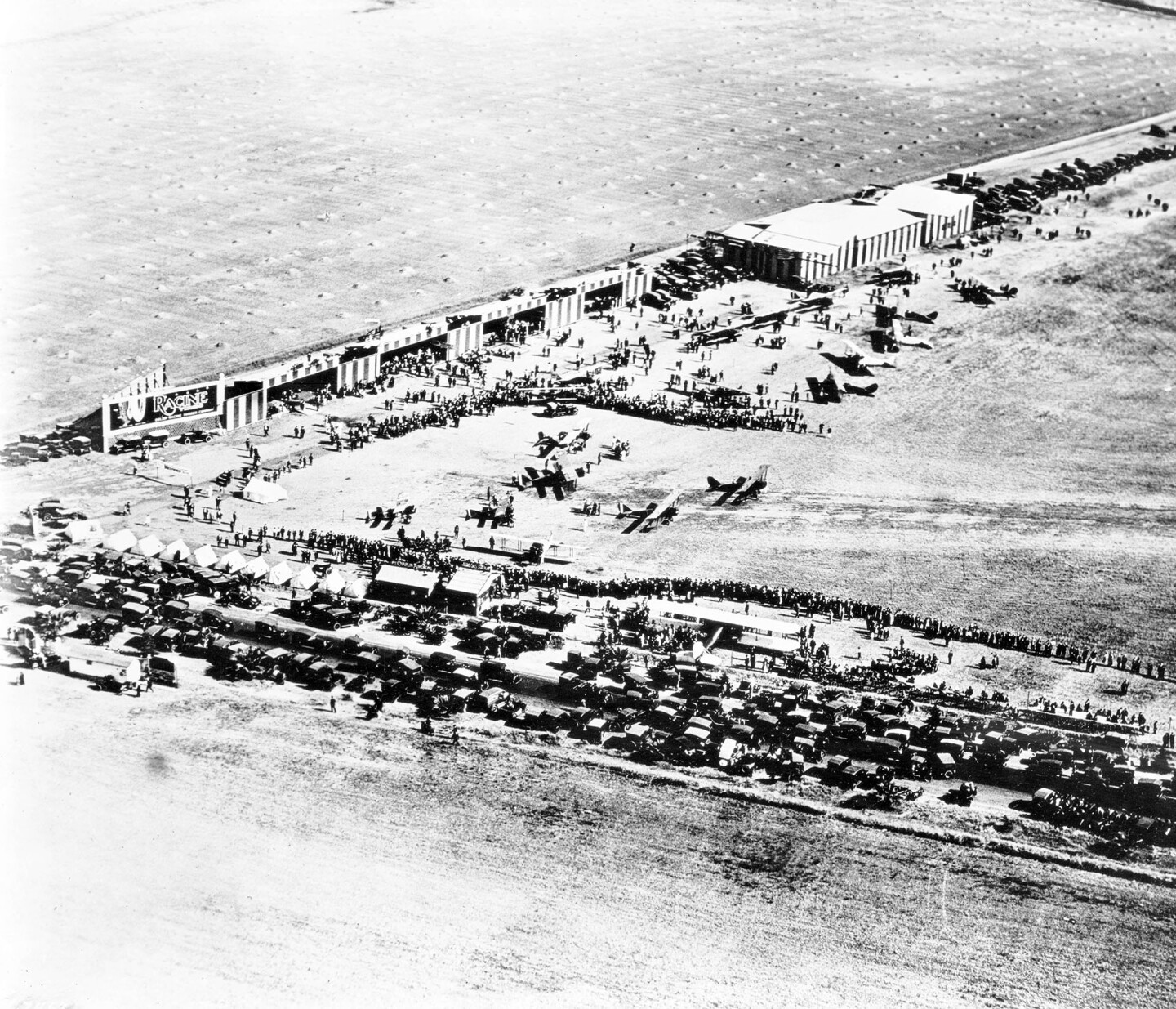 Aerial view looking southeast on crowds at Sid Chaplin's airport at the intersection of Wilshire Boulevard and Fairfax Avenue, Los Angeles, 1920