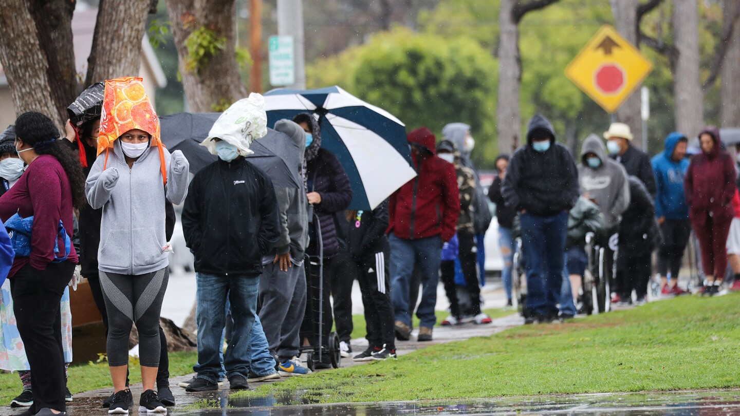 People wait in line to receive food at a Food Bank distribution for those in need as the coronavirus pandemic continues on April 9, 2020 in Van Nuys, California. | Mario Tama/Getty Images