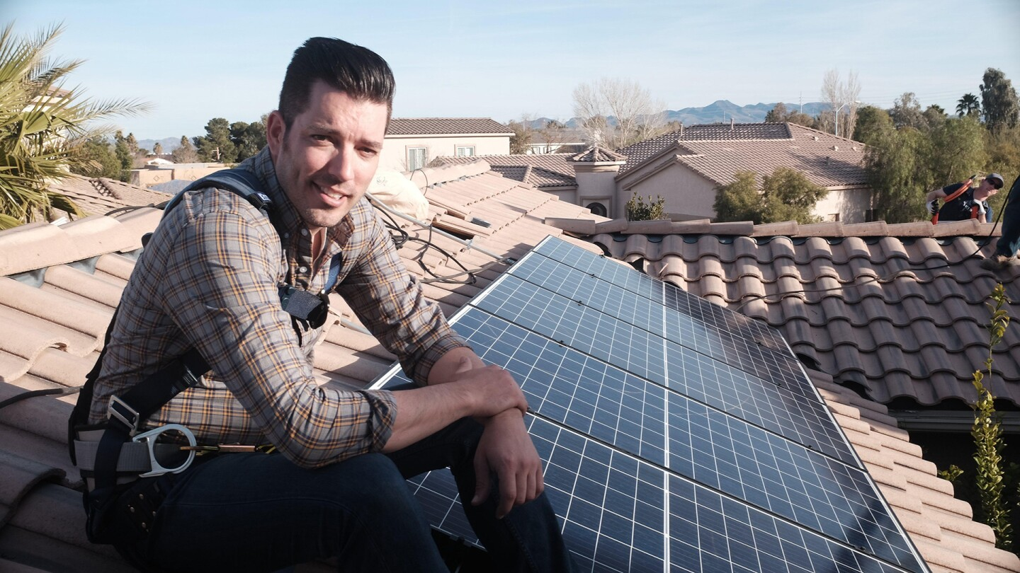 Jonathan Scott sits atop a roof next to solar panels.