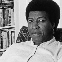 Patti Perret, photograph of Octavia E. Butler seated by her bookcase, 1986. The Huntington Library, Art Collections, and Botanical Gardens. © Patti Perret