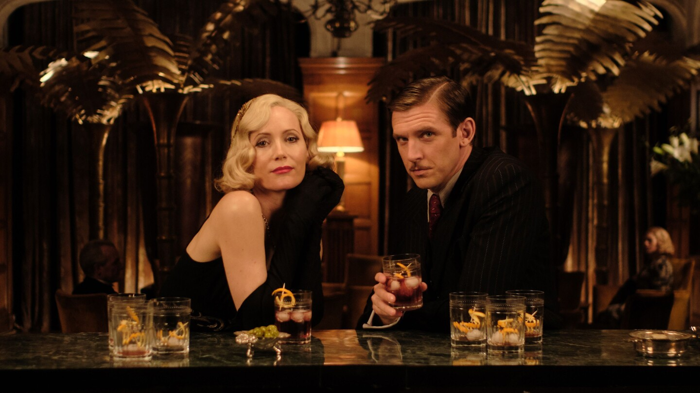 Leslie Mann and Dan Stevenson pose at a lavish bar with drinks on the counter surface.