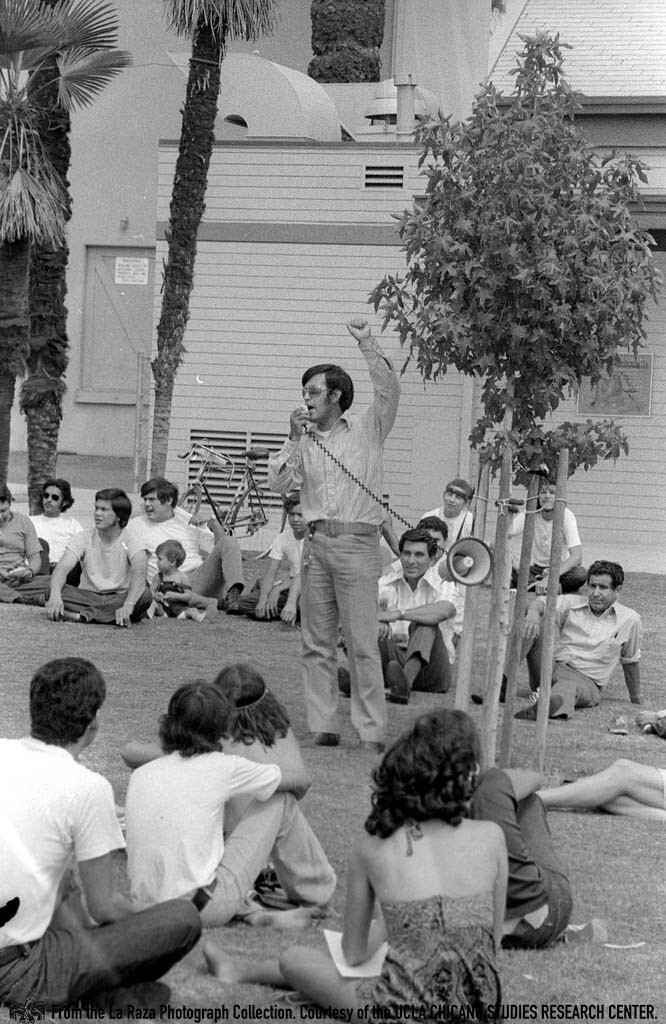 CSRC_LaRaza_B14F6S1_N005 Man, possibly Nacho Uribe, speaks to a crowd at Chicano Moratorium anniversary | Patricia Borjon Lopez, La Raza photograph collection. Courtesy of UCLA Chicano Studies Research Center