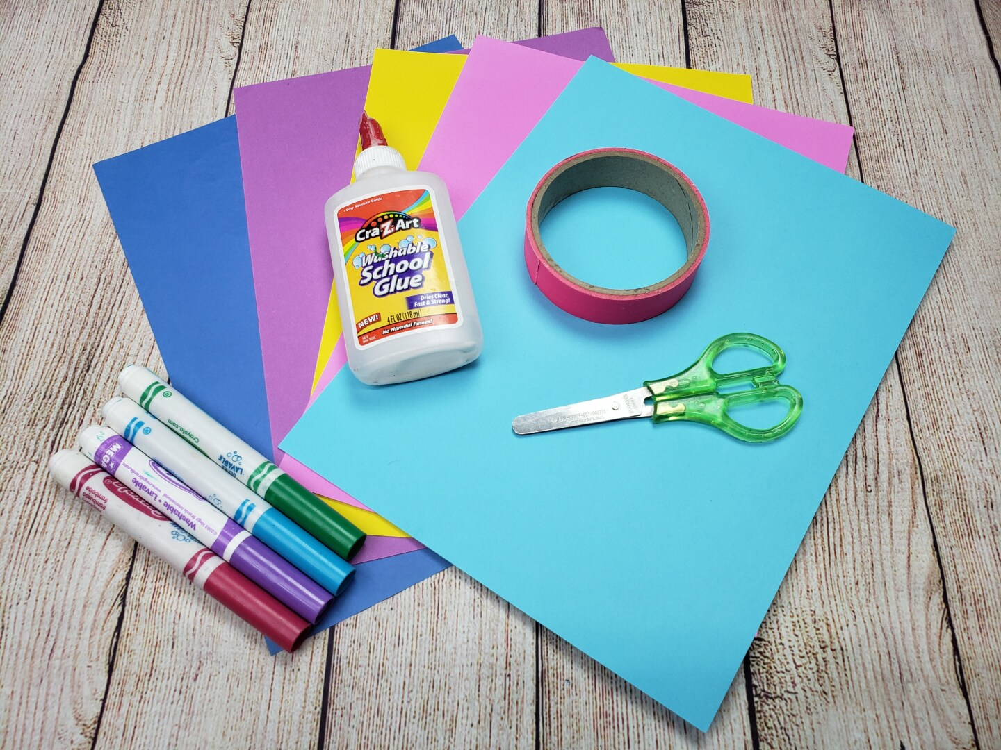 construction paper, markers, glue, tape and scissors are laid out on a wooden table