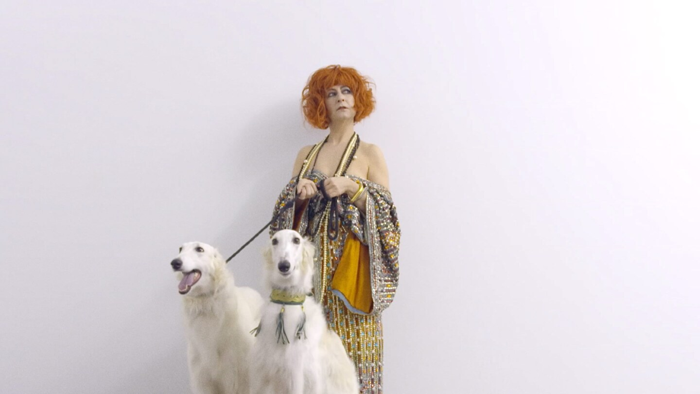 "Still from Border Blaster 506, ""Rhythmic Rituals:"" A woman stands in front of a white hall with two white dogs on leashes."