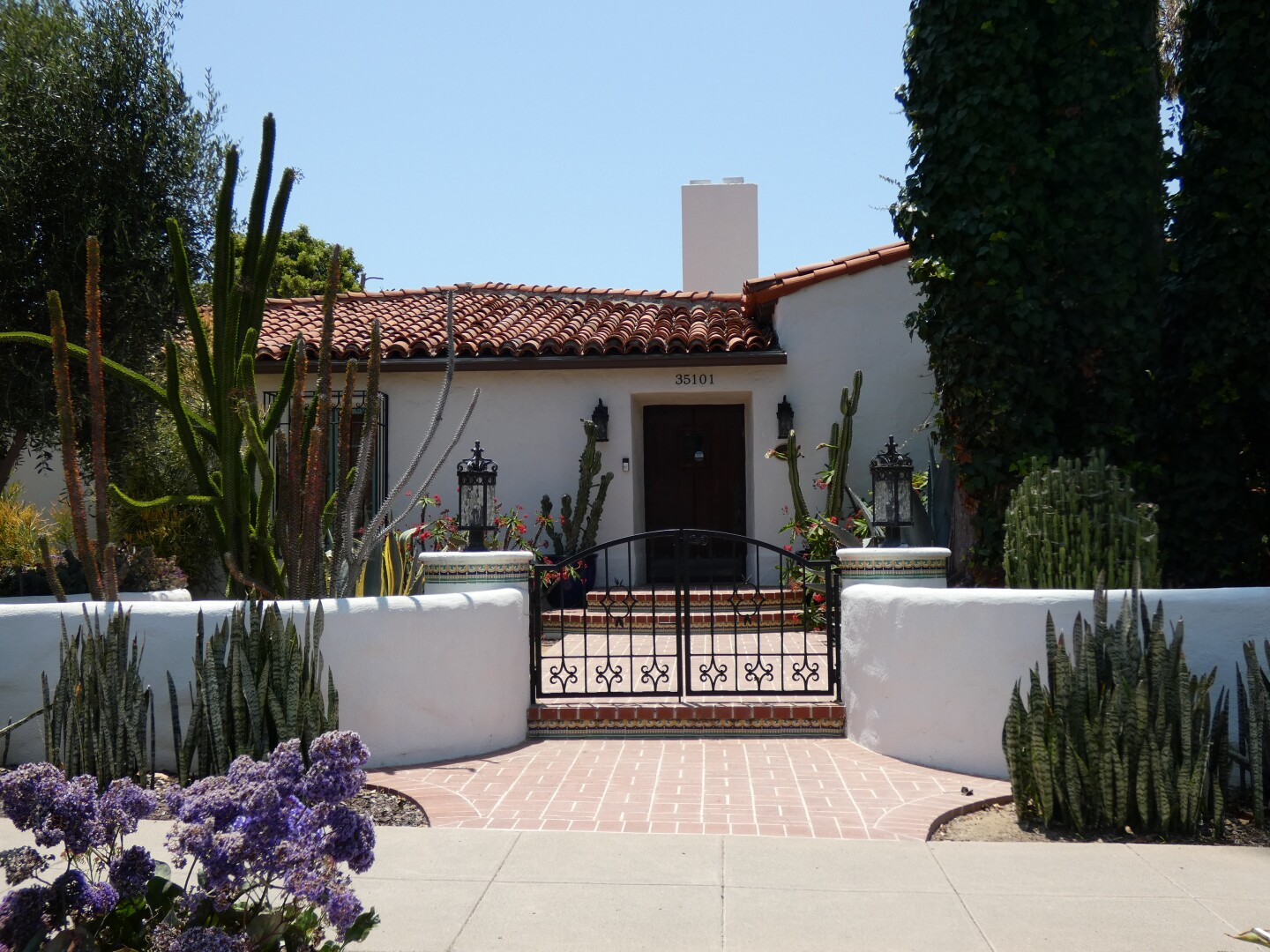 A Spanish Colonial Revival-style house features a red-tiled roof, an ornate black gate and a short white wall at its front. Various cacti and other foliage decorate the house's front.