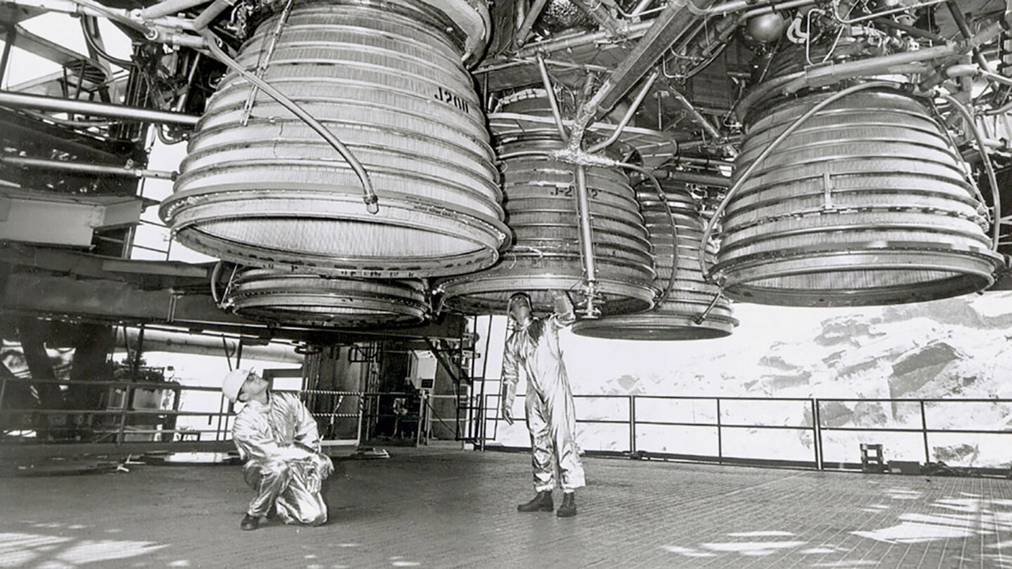 Two workers are dwarfed by five Rocketdyne J-2 engines of the Saturn V second stage (S-II) as they make final inspections prior to a static test firing by North American Rockwell's Space Division. | Courtesy of NASA