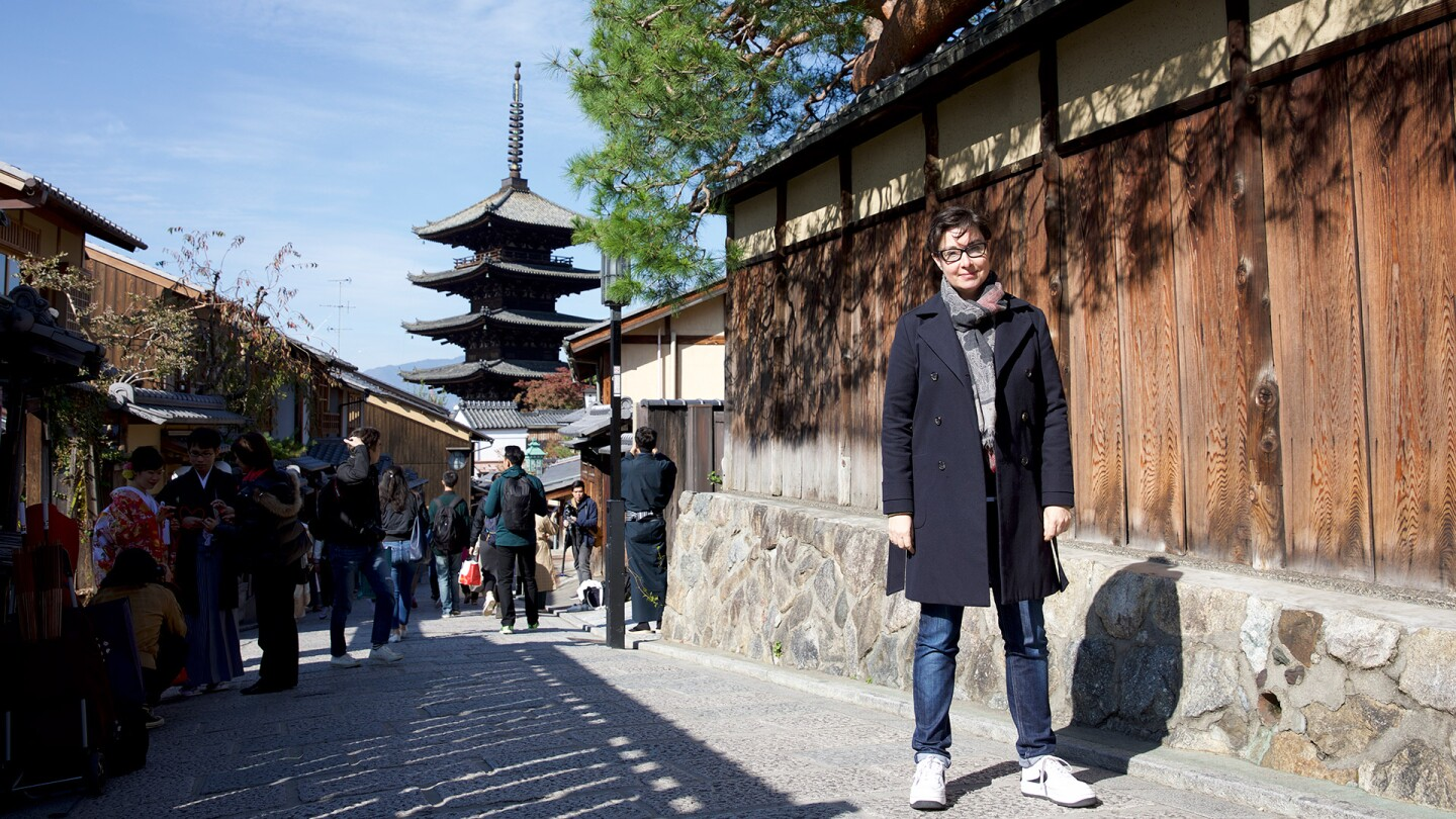 "Sue Perkins stands in a small street in Japan with a pagoda in the background. | From ""Japan with Sue Perkins"""