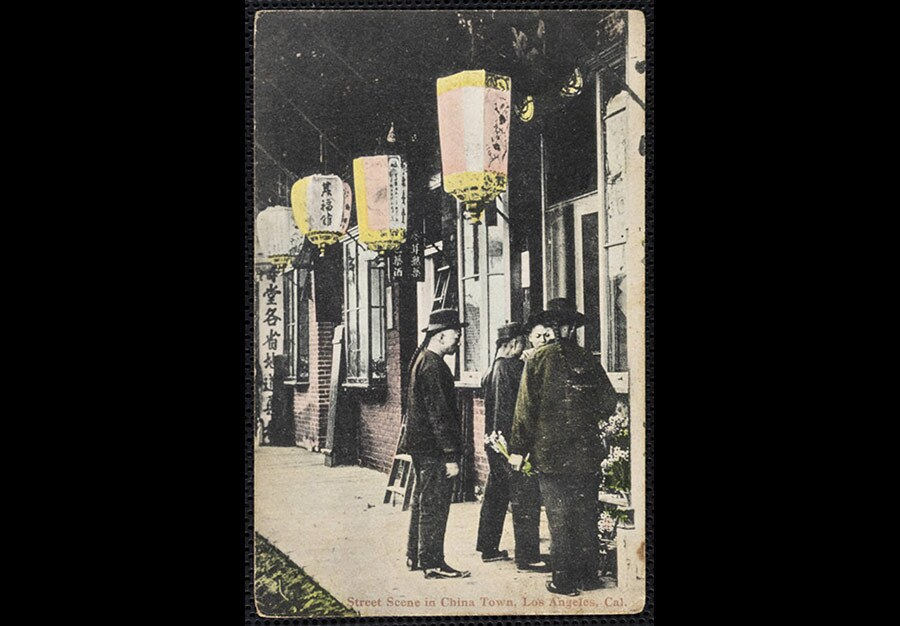 """A color postcard reads """"Street Scene in China Town, Los Angeles, Cal."""" In it, four men in black, all wearing queues, stand near a storefront at a brick building with paper lanterns."""