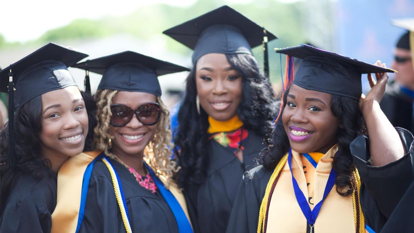"A group of Black women in college graduation garb pose for a picture. | From ""Independent Lens: Tell Them We Are Rising"""