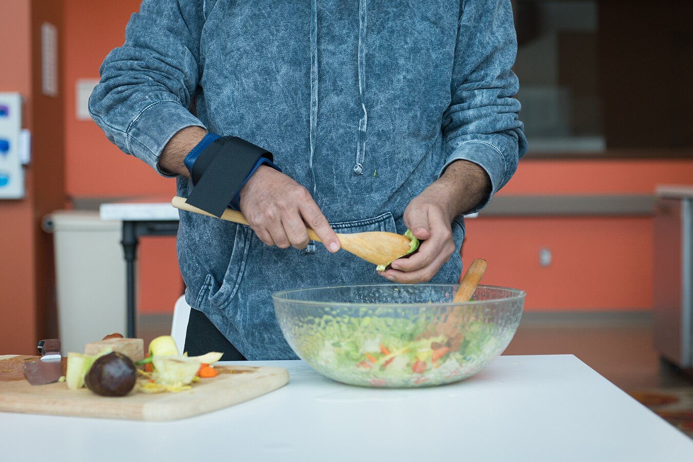 Perez's hands trembled as he tried to cut vegetables, so a weighted band was wrapped around his wrist to help keep him steady.