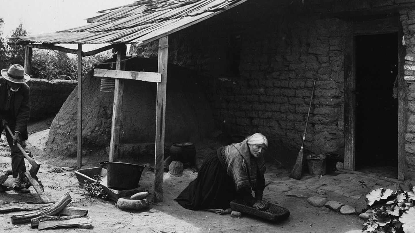 A Tongva man and woman work outside their home