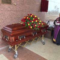 Father Albert Avenido standing next to Eileen Neri's casket at her funeral. No one was allowed to attend because of COVID-19.