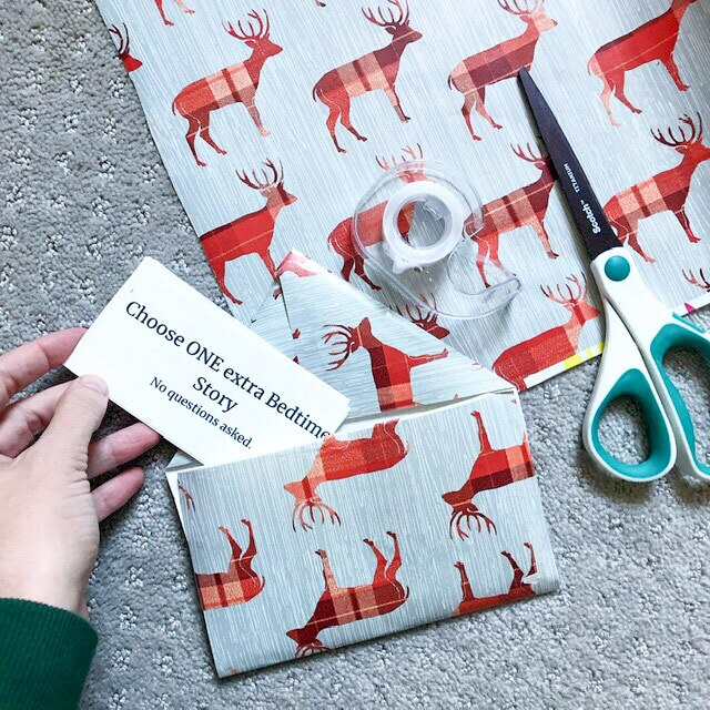 """An envelope made out of wrapping paper with red reindeer on it holds a note that reads """"choose one extra bedtime story"""""""