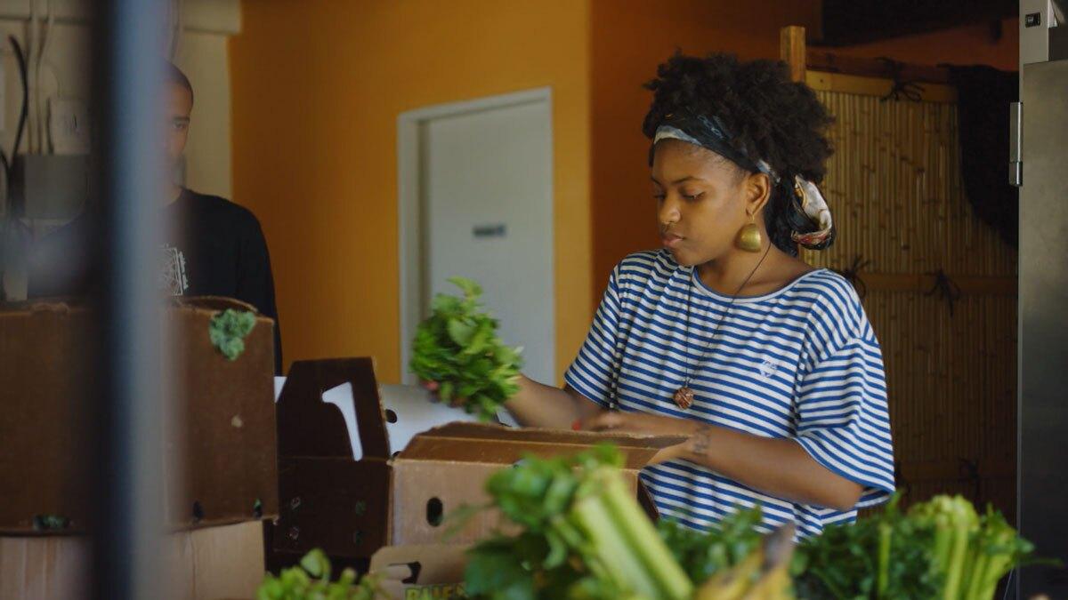 "Olympia Auset arranging produce   Still from ""Broken Bread"" Access"