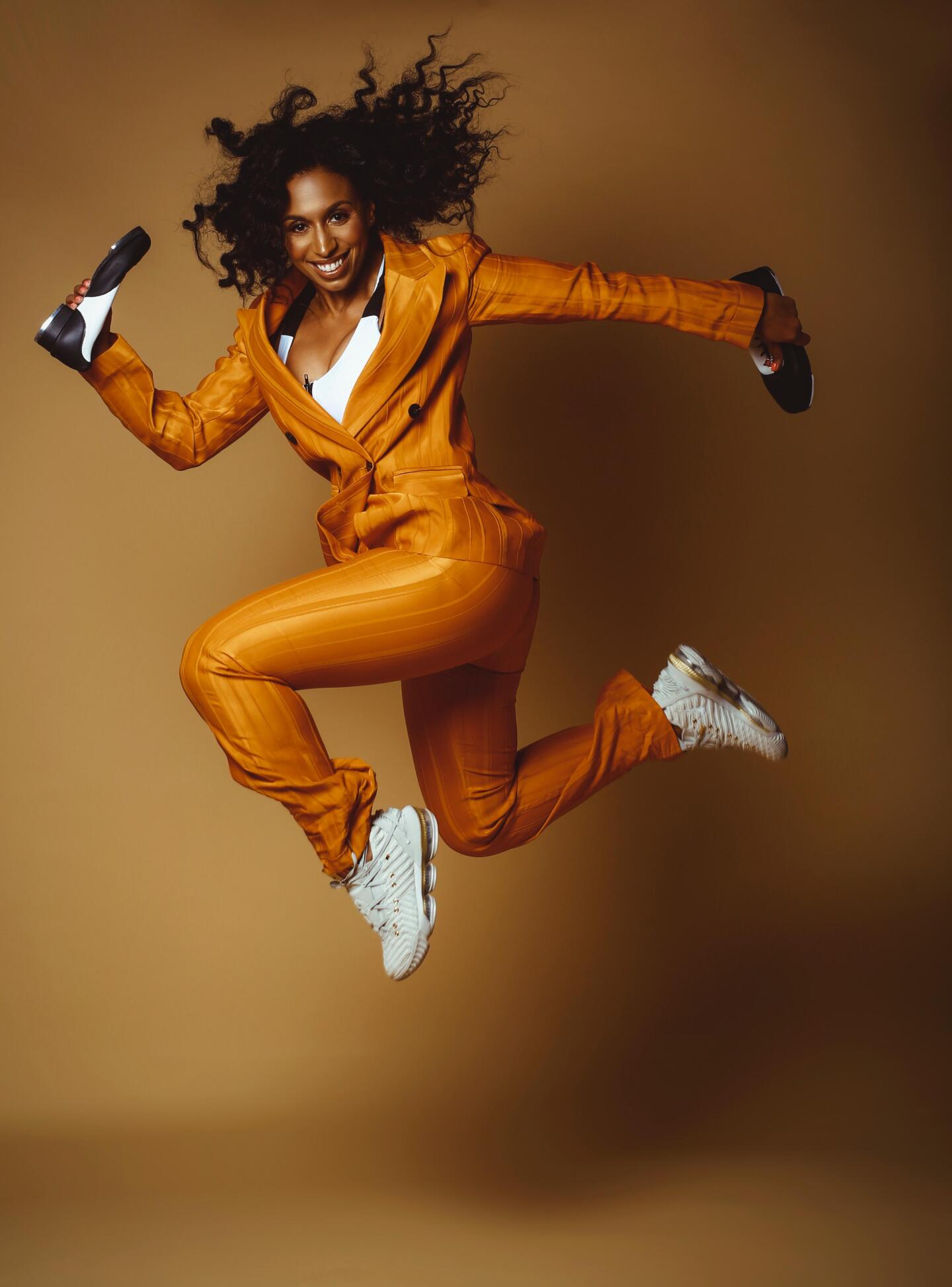Chloe Arnold in flight wearing a suit and sneakers.