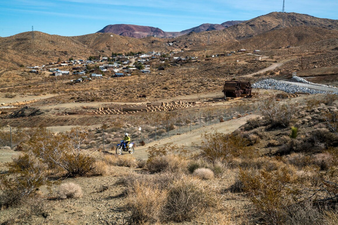 A solo dirt bike rider motors by Randsburg's defunct mill site that is considered by federal authorities to be highly contaminated with arsenic from historic mining activity in the area. | Kim Stringfellow.