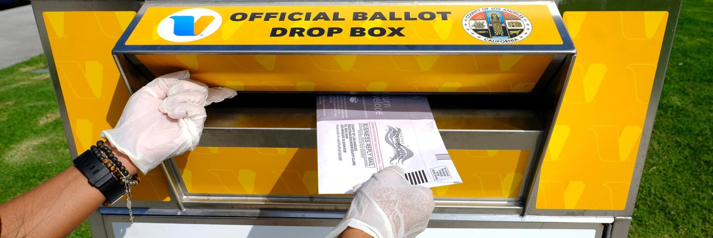A woman wearing protective gloves posts her election ballot in an official ballot drop box on October 20, 2020 in Marina del Rey, California.   Amanda Edwards/Getty Images