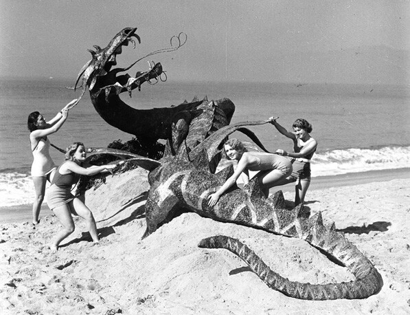 Women subdue a (fake) dragon on a Los Angeles beach, circa 1940. From the Los Angeles Area Chamber of Commerce Collection