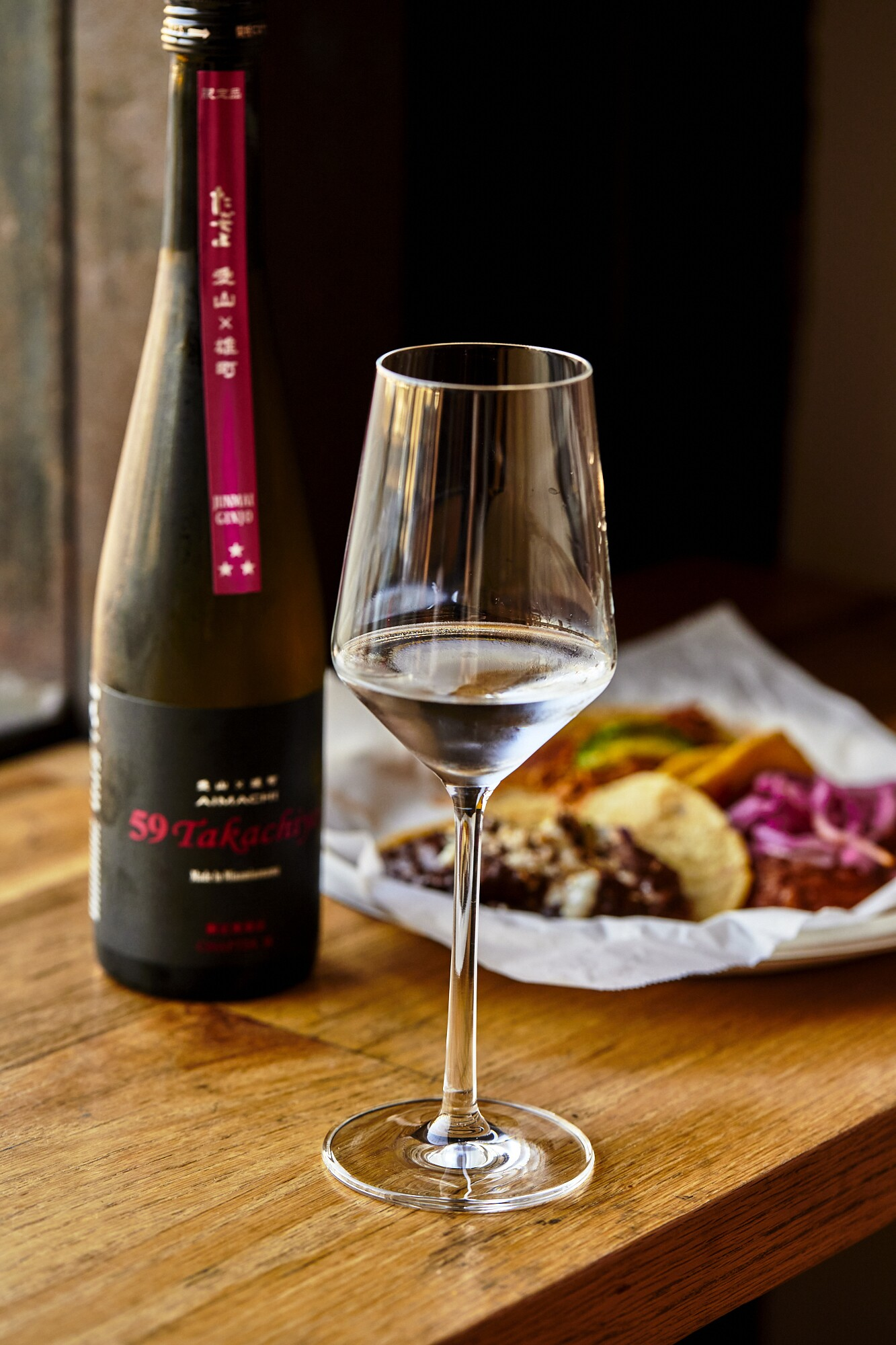 A bottle of unpasteurized nama in a wine glass is set in front of street tacos.