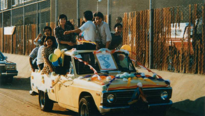 A group of young Vietnamese Americans ride in a brightly decorated car.