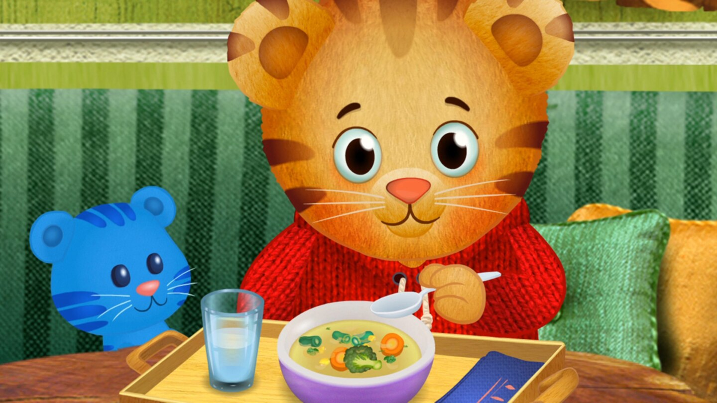 Cartoon of a small tiger sitting at a table eating a bowl of soup/