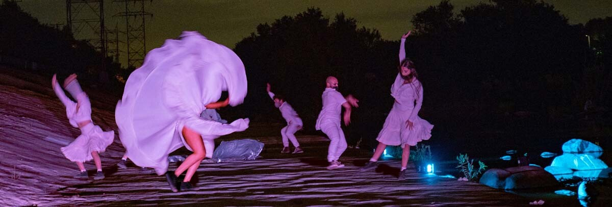 "Dancers performing by the Los Angeles River banks at night. The performance is part of at ""Firefly Nights,"" an in-person COVID-safe experience that falls within the ""Rio Reveals"" series."