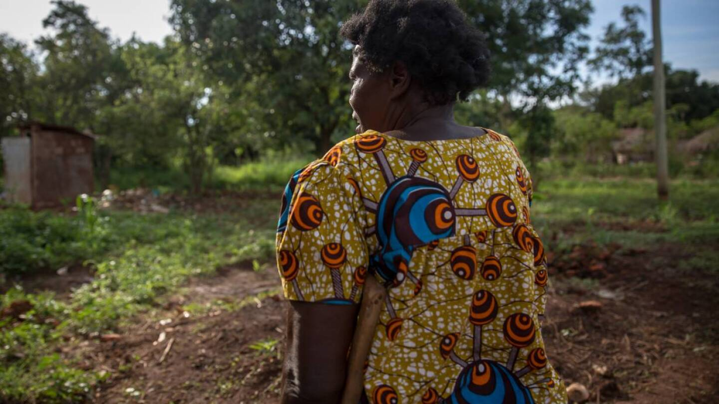 Matina, 67, stands in front of the plants she is growing to feed the seven children she supports. She is skipping her antiretroviral medication because it hurts her stomach to take it without food. Gulu, Uganda. | Thomson Reuters Foundation/Sally Hayden