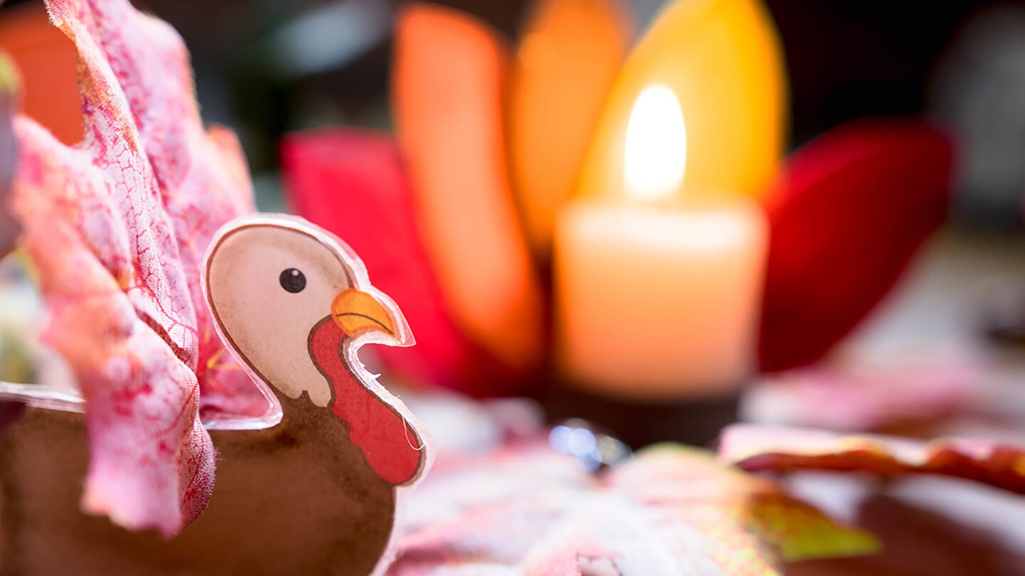 A small turkey craft in front of a candle