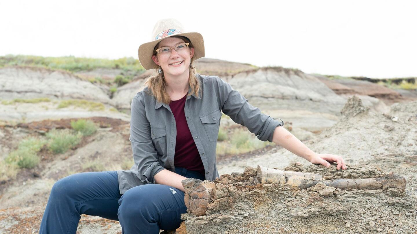 """Emily Graslie poses for a photo on some rocks. 