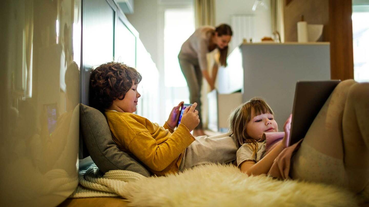 two children relax on the floor while watching their devices