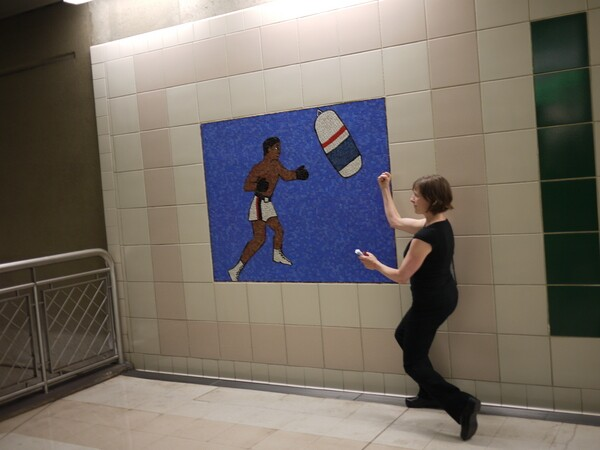 Artist Sara Wookey prompts tour participants to pose like their favorite sports portrait along a wall at the Civic Center station | Photo: George Villanueva