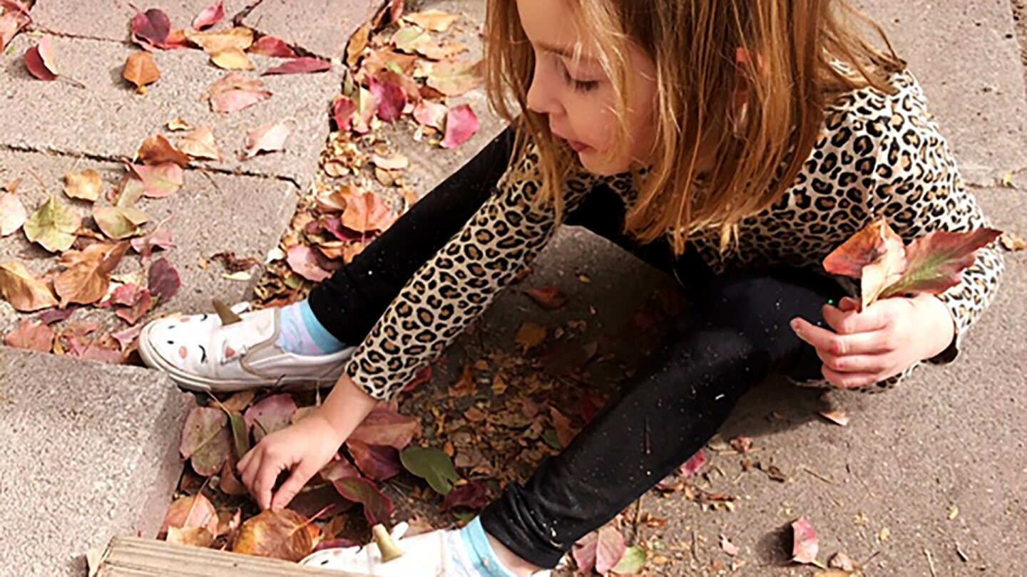 A small blonde girl sits on the floor gathering leaves