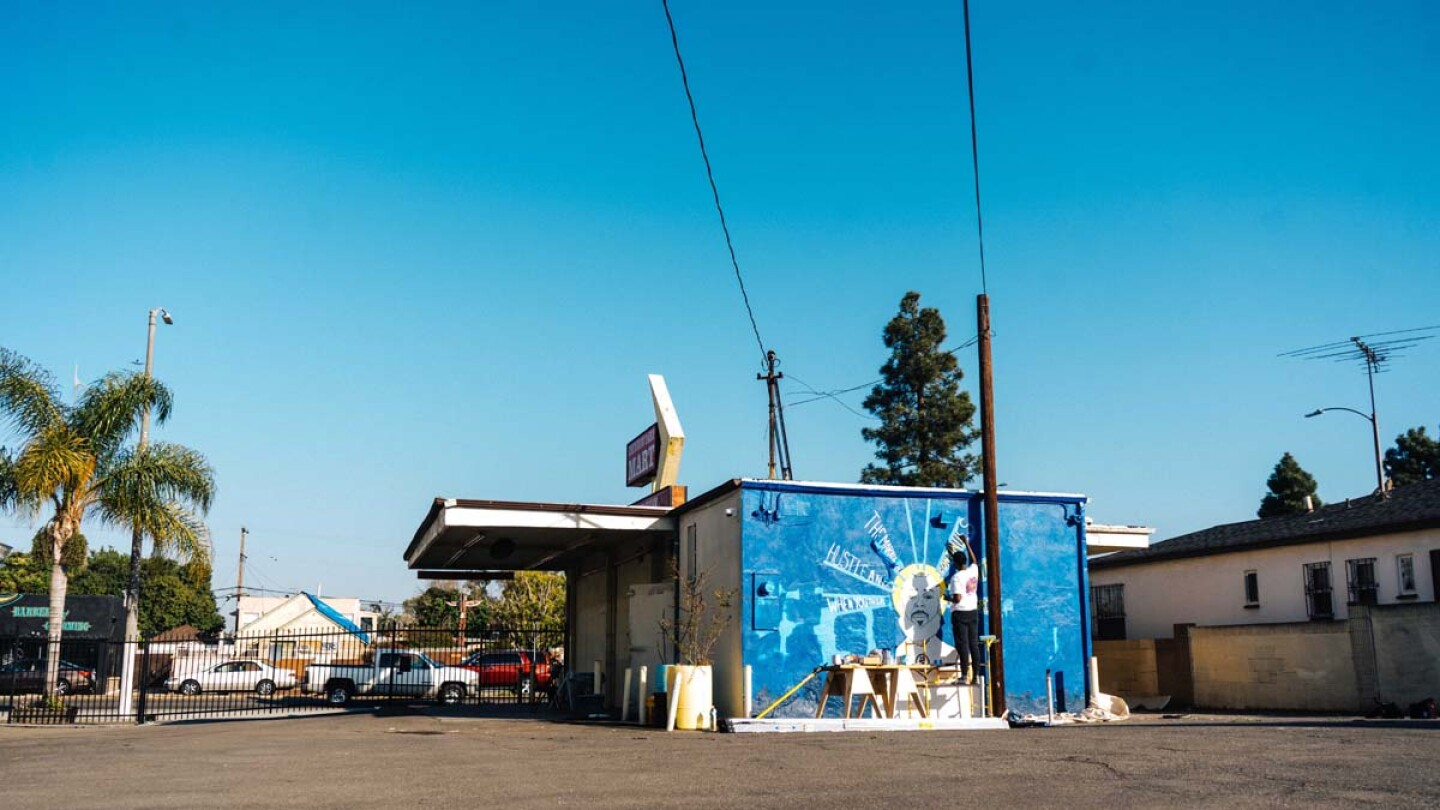"""A wide shot of the Crenshaw Dairy Mart showing artist Oto-Abasi Attah painting a mural of Nipsey Hustle, """"Saint Nip"""" 