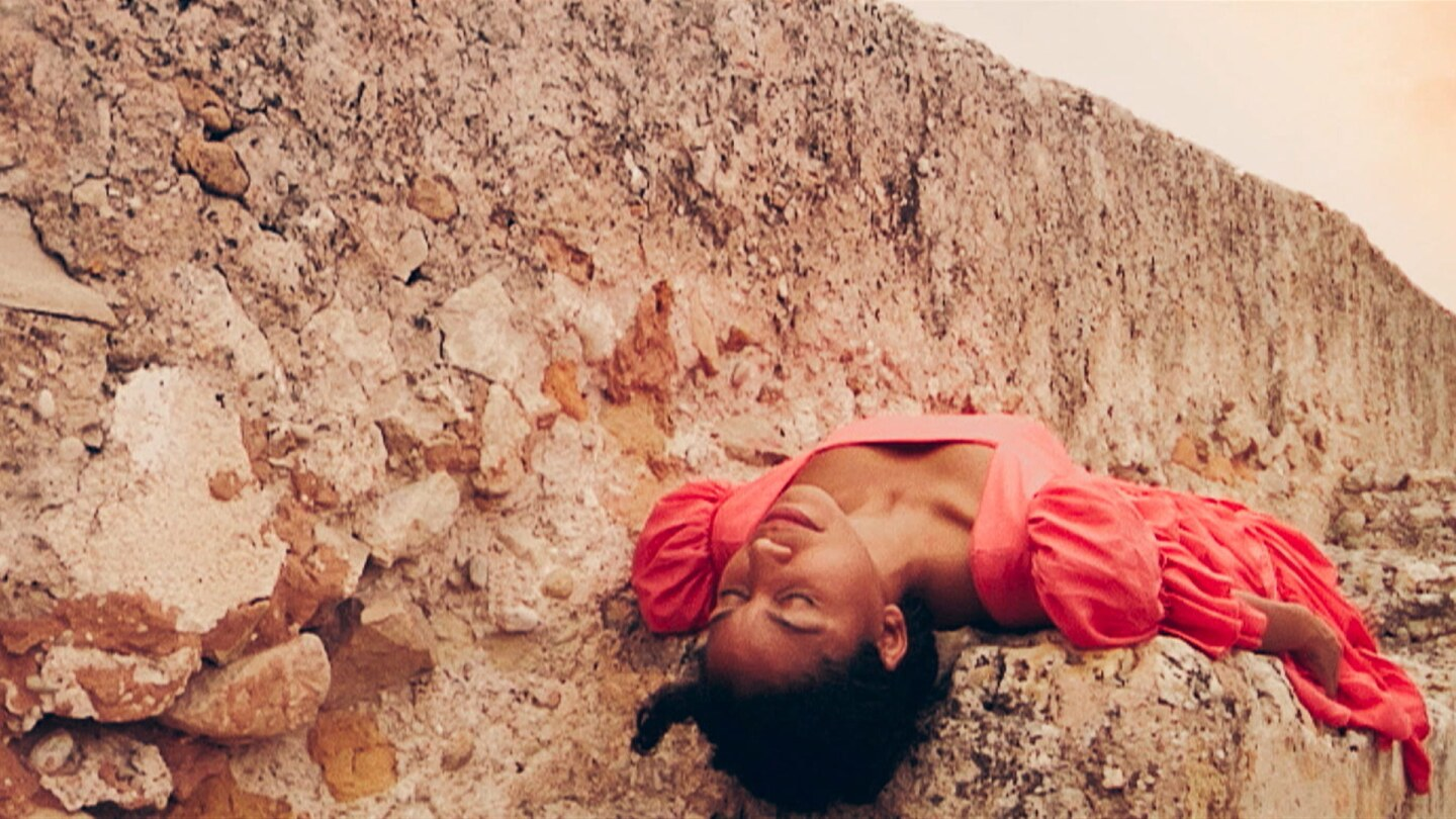 """Still from """"Watching You:"""" A woman in red clothing lies on her back in a rocky environment."""