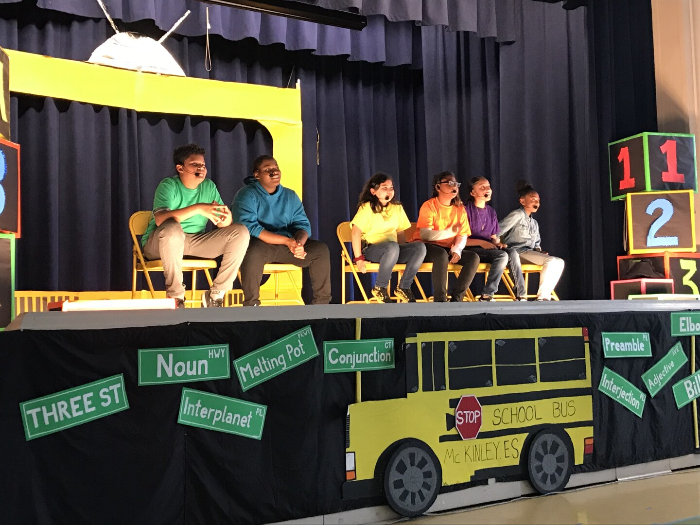 Students sit on stage in answering questions from the audience of McKinley K-8 School of Integrated Arts.