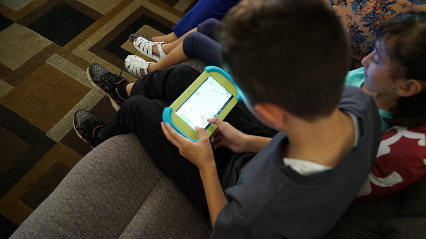 A young boy and young girl using educational tablets.
