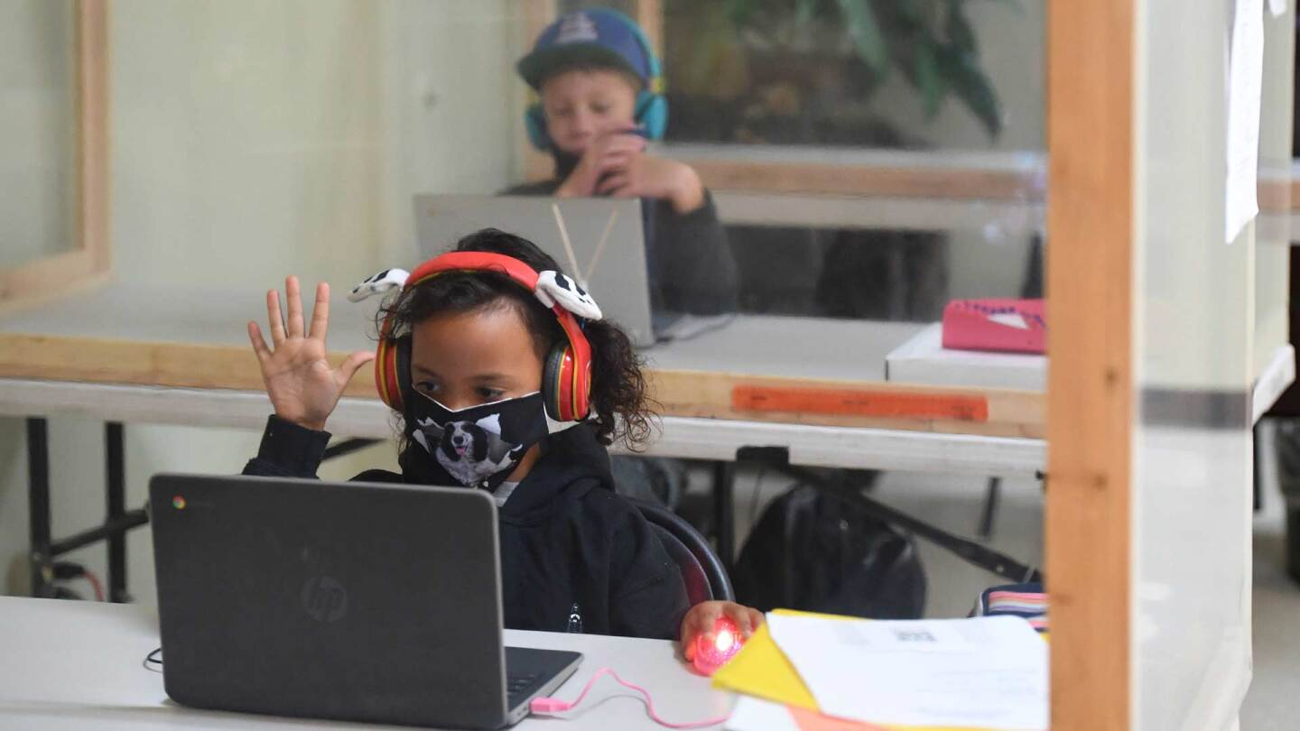 Students follow along remotely with their regular school teacher's online live lesson from separated by plastic barriers at STAR Eco Station Tutoring & Enrichment Center on September 10, 2020 in Culver City, California
