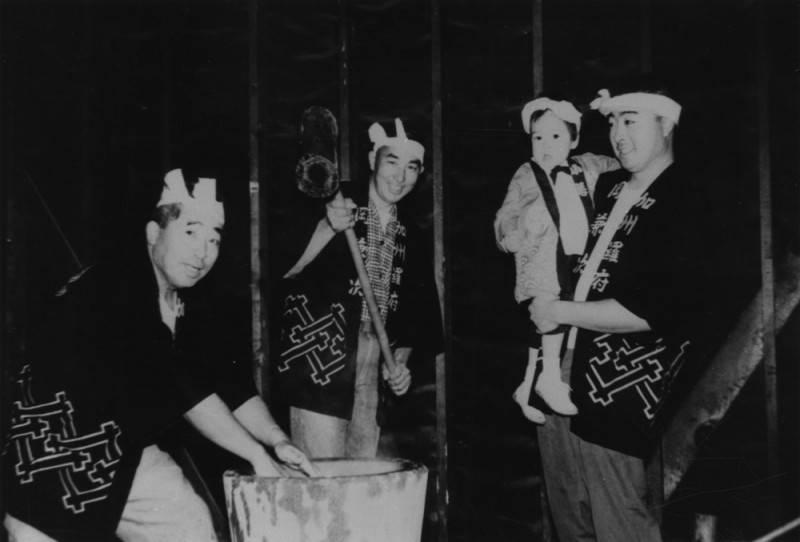 Black and white photograph of Takashi Kato, Bill Chomori, Jennifer and Roy Kato as they make mochi, 1964.
