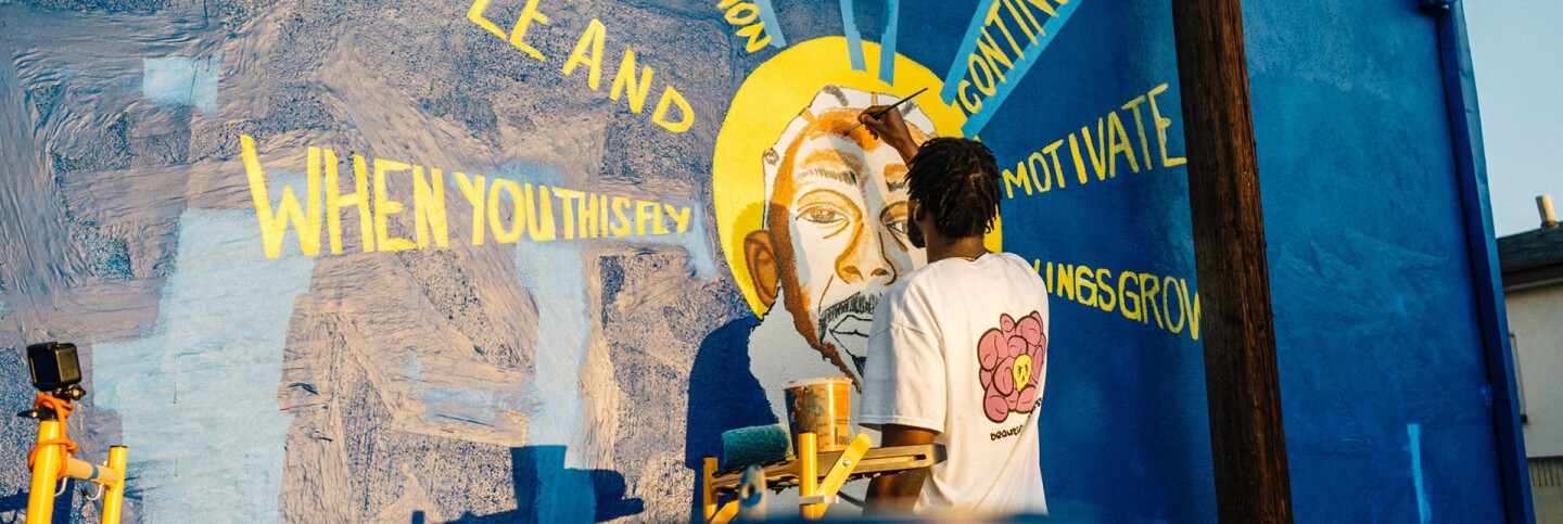 """Visiting artist Oto-Abasi Attah from Nigeria and raised in Los Angeles paints a mural of Nipsey Hustle, """"Saint Nip"""" at the Crenshaw Dairy Mart   Courtesy of Crenshaw Dairy Mart"""