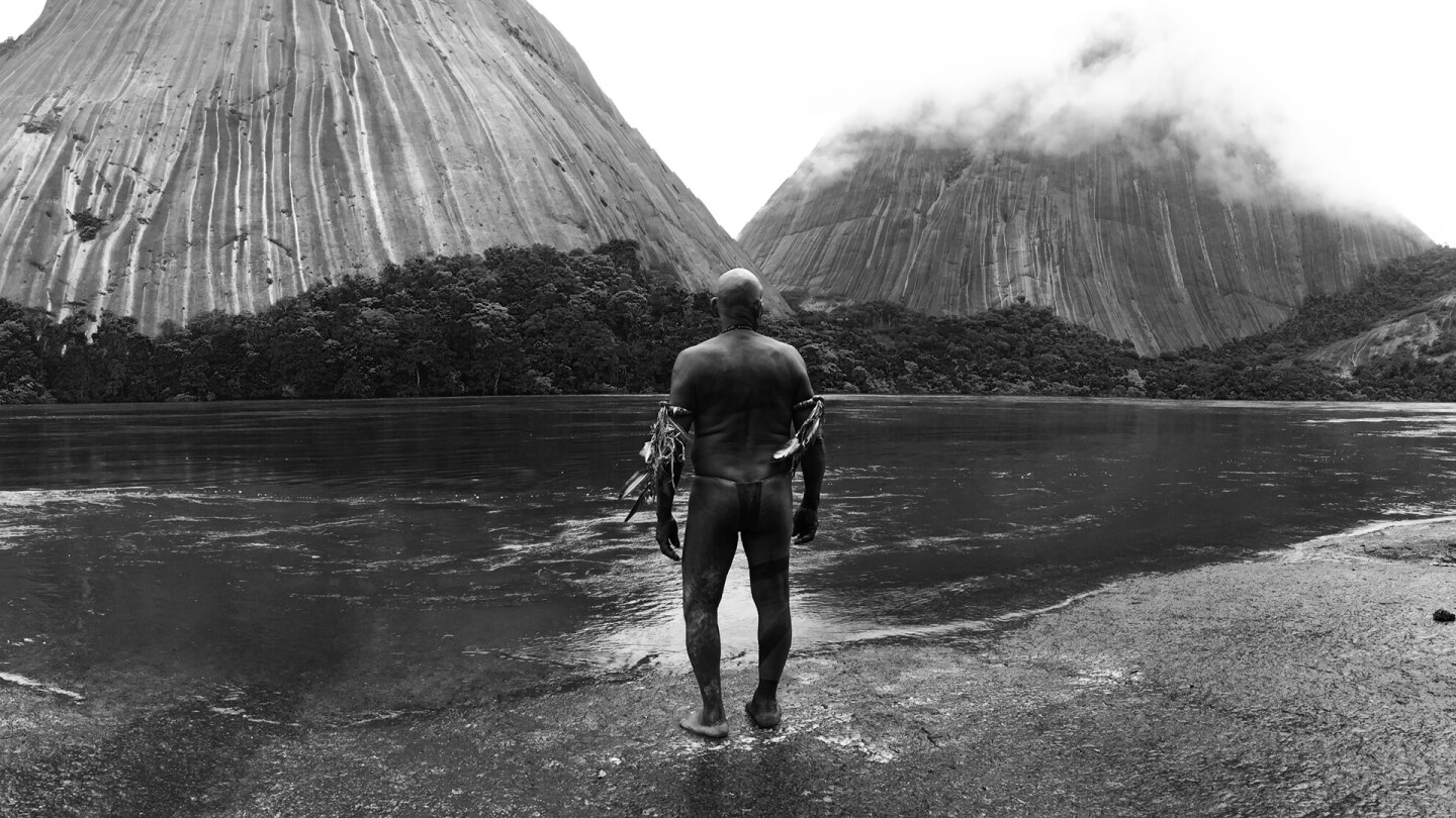 "A man looks out to a vast landscape of mountains and water. | From ""Embrace of the Serpent"" / Kino Lorber"