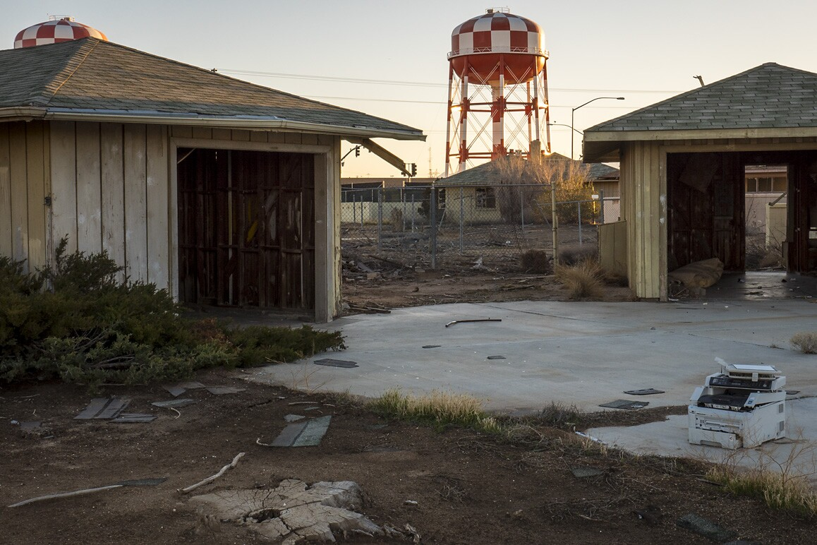 Empty garages of George Air Force Base's former housing with a water tower serving Victorville's Federal Correctional Complex in the distance. Photo: Kim Stringfellow.