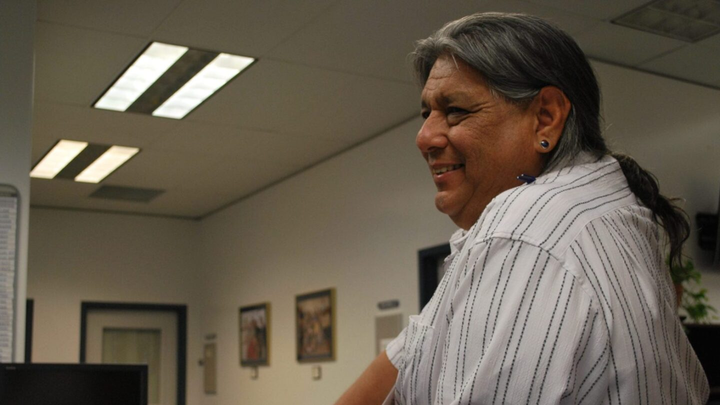 Side photo of an Indigenous man who is smiling inside an office. He is wearing his long hair in a ponytail and wears a striped button down shirt.
