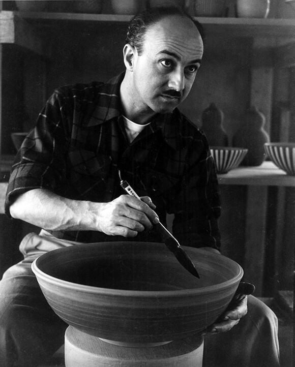 Harrison McIntosh applies brush work to a large bowl in his first studio, Foothill Blvd., Claremont, CA, c. 1953