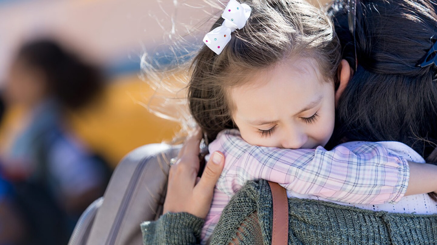 A small child hugs a caregiver goodbye in front of a school bus.
