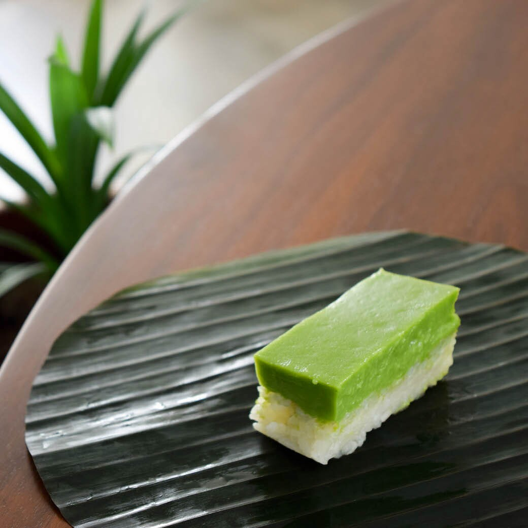 Kueh salat (a cousin of Teochew gue) is a popular Malaysian cake with pressed sticky rice layered with coconut egg custard flavored with pandan.