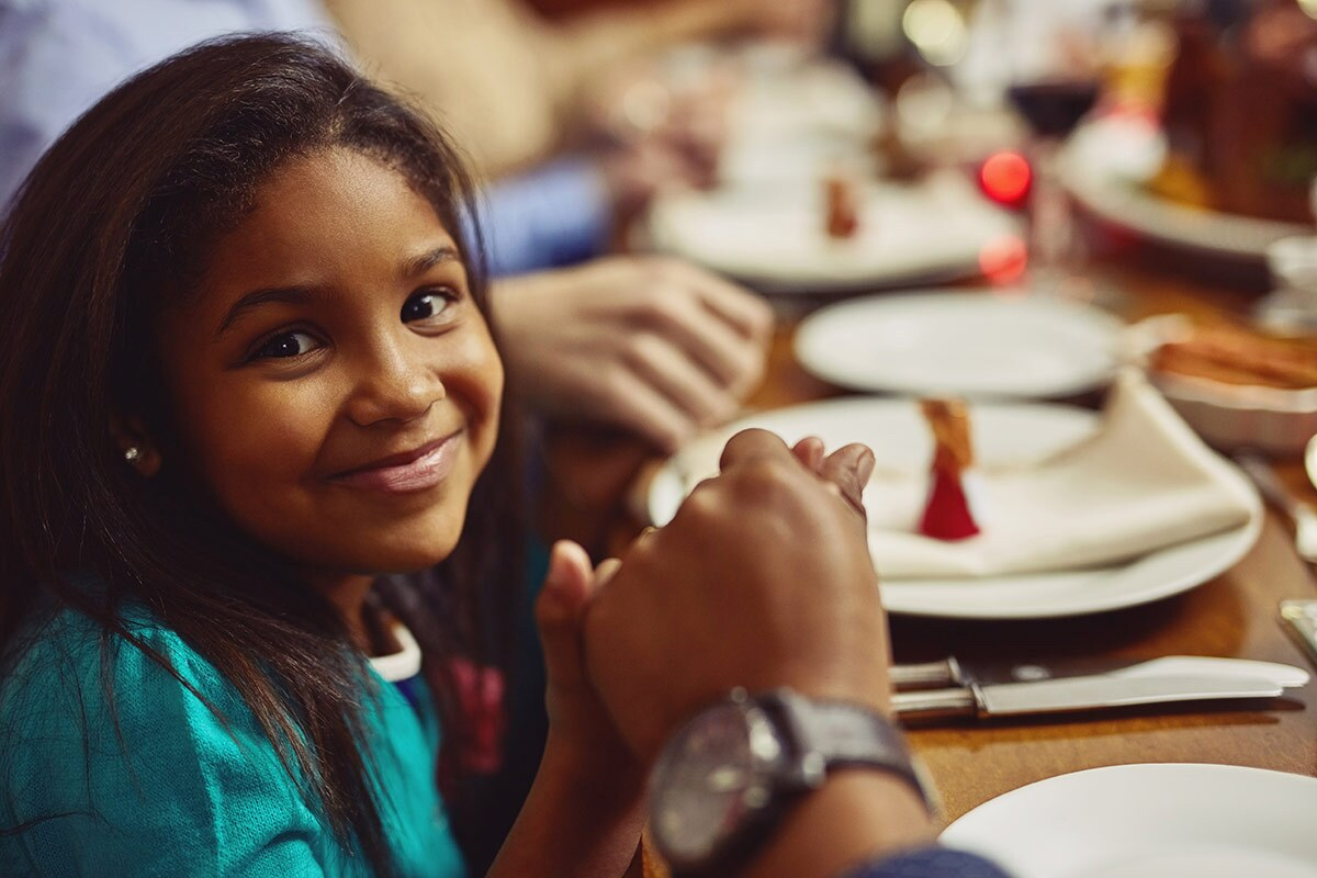 Portrait of an adorable little girl holding hands in prayer with her family before having a meal together. iStock